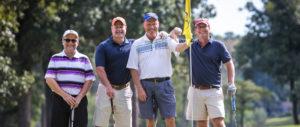 4 men smiling while playing golf