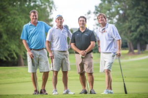 4 men on the golf course smiling