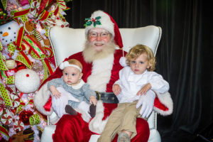 two kids on santas lap at the holiday show