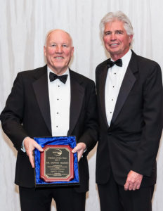 two men posing with the citizen of the year award