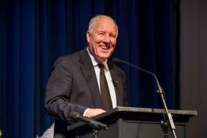 a man at a podium smiling