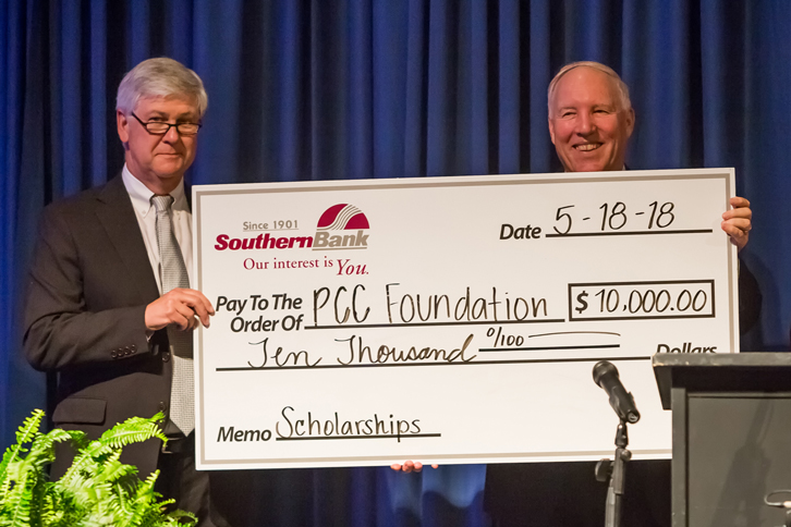 A Southern Bank representative and Dr. G. Dennis Massey hold a check announcing the creation of a new scholarship with the PCC Foundation to honor the retiring president.