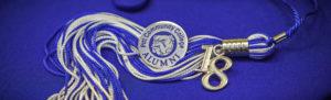 PCC Alumni pin and graduation tassel on blue background.