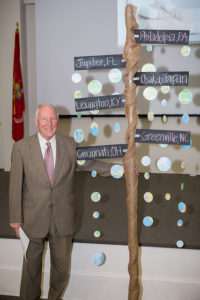 dr massey standing next to a pole with cities on it