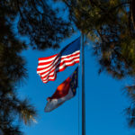 US and North Carolina flags flap in the breeze with clear, blue sky in background and pine trees on each side.