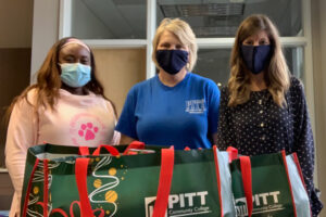 PCC Counseling Department staff members Mecca Waller, Kimberly Williamson and Olivia Sutton (left to right) practice coronavirus safety measures as they prepare to distribute food items to students in need of assistance.