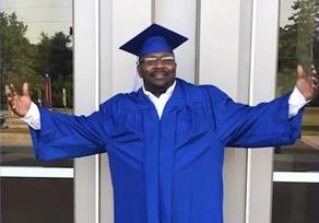 Perry White wearing graduation regalia.