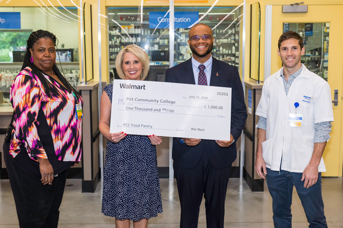 Photo of two Walmart representatives presenting a check to a pair of PCC representatives.