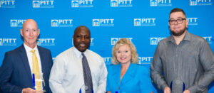 Group photo of four PCC Alumni Award recipients standing in front of PCC Blue background with Pitt logos.