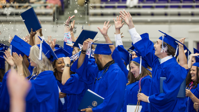 Graduates dressed in their blue cap and gowns celebrating.