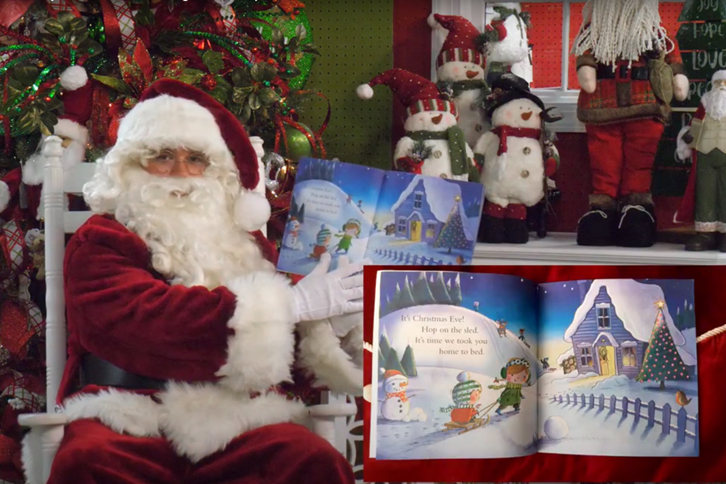 Santa Claus sitting in front of Christmas tree holding children's storybook.