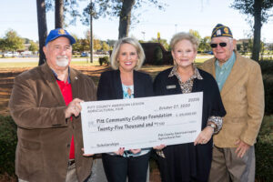 Check presentation photo with four people holding a large, ceremonial check.
