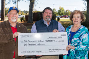 Three people holding large ceremonial check representing Pitt County Fair donation to PCC's Horticulture Technology program.