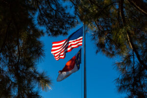 American and North Carolina flags flap in breeze against blue sky and framed by pine trees.