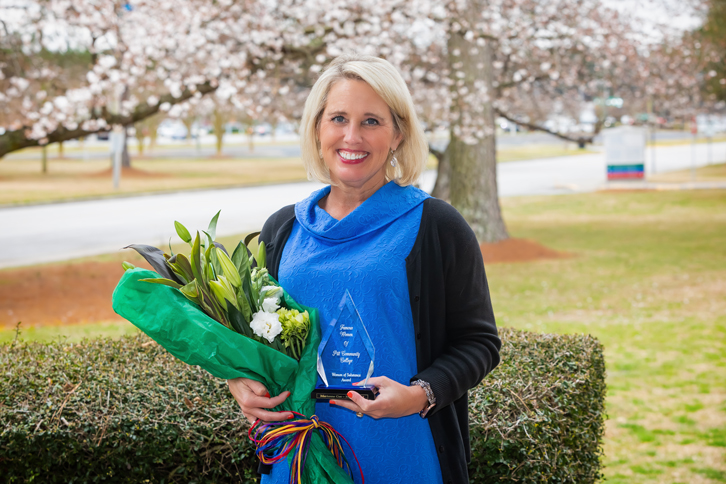 Marianne Cox holding WOS Award and flowers.