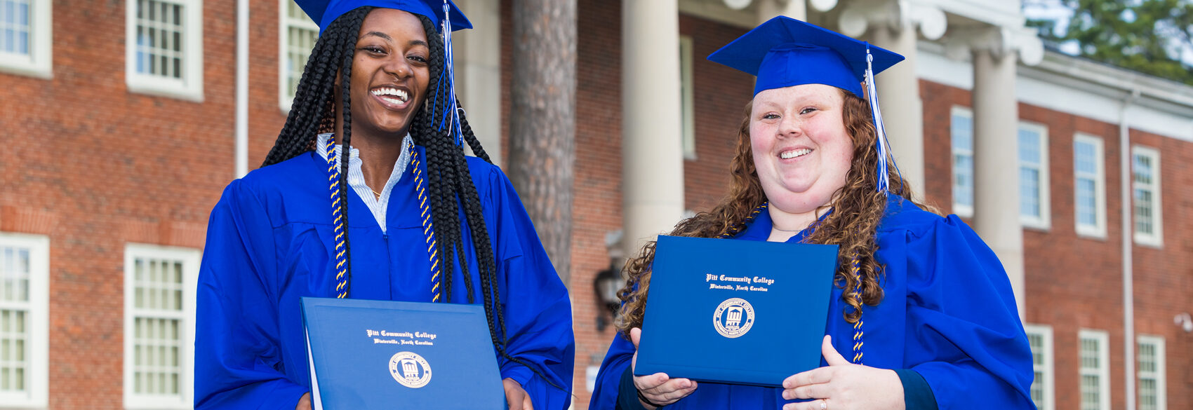 A pair of PCC graduates wearing their caps and gowns smile outside of the Humber Building