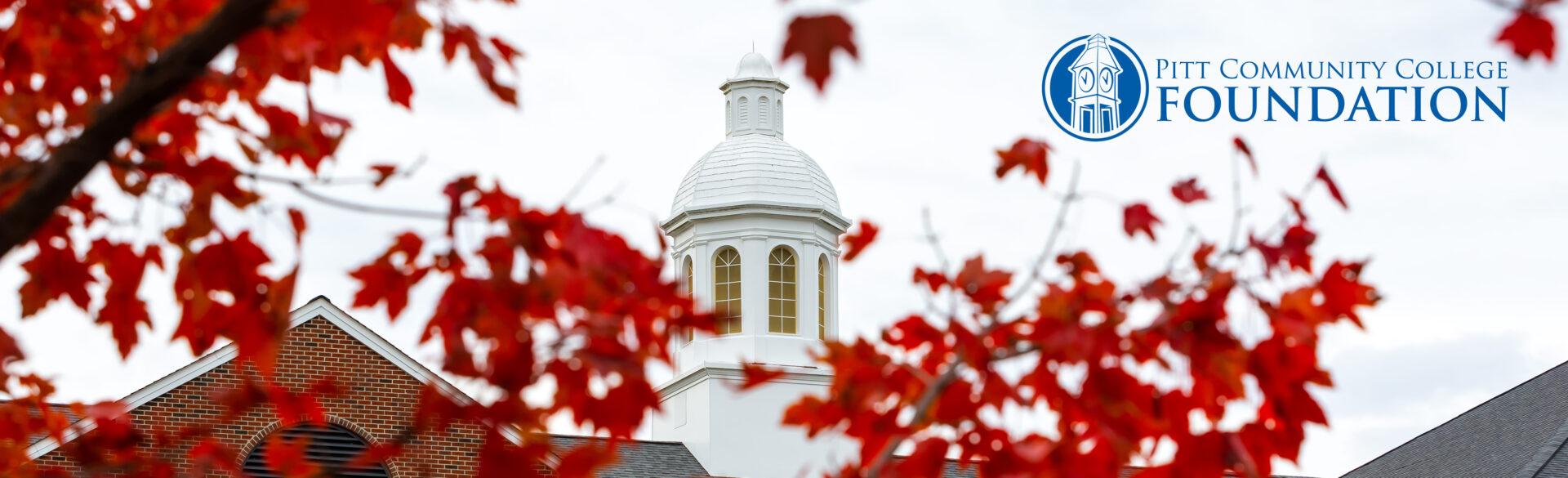 Warren Cupola framed by orange fall leaves.